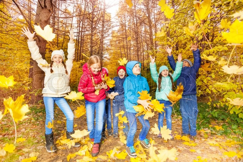 Happy excited kids playing together with flying yellow leaves in forest during autumn daytime, stock photo