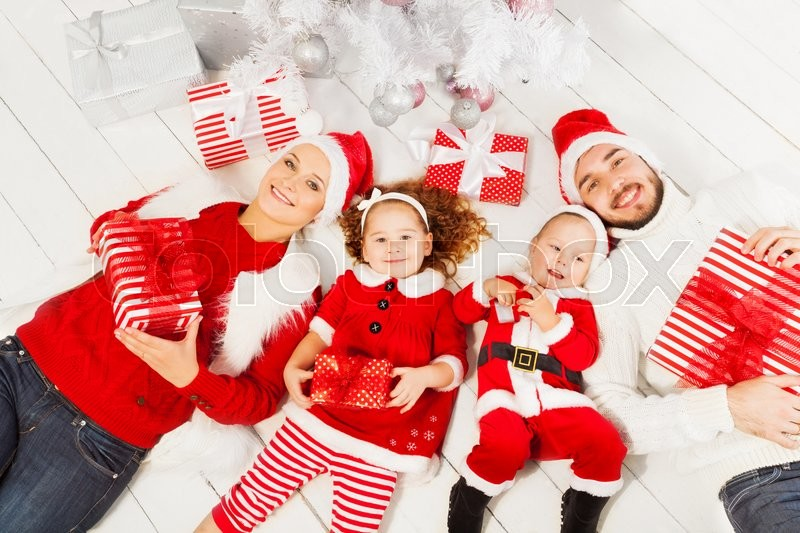 Family with little boy and girl lay under the Christmas tree with presents, view from above happy smiling , stock photo