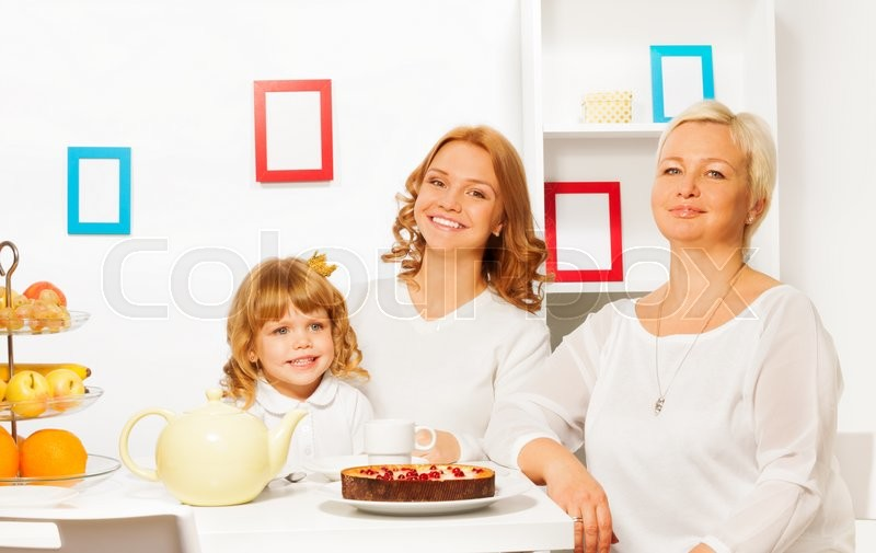 Happy family mother father and granddaughter eating cake by the table with smile, stock photo