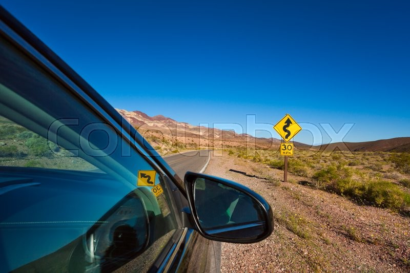 Car stopped on the road with arrow yellow sign in desert, California, United States, stock photo