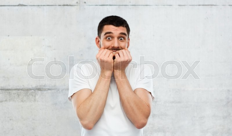 Emotion, advertisement and people concept - scared man in white t-shirt over gray wall background, stock photo