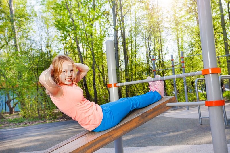 Blond girl curls up on the wooden board at the sports ground during summer sunny day outside, stock photo