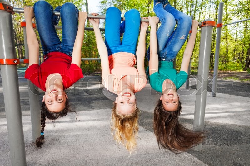 Three girls hanging upside-down on the brachiating bar at the sports ground during summer day with trees on background, stock photo
