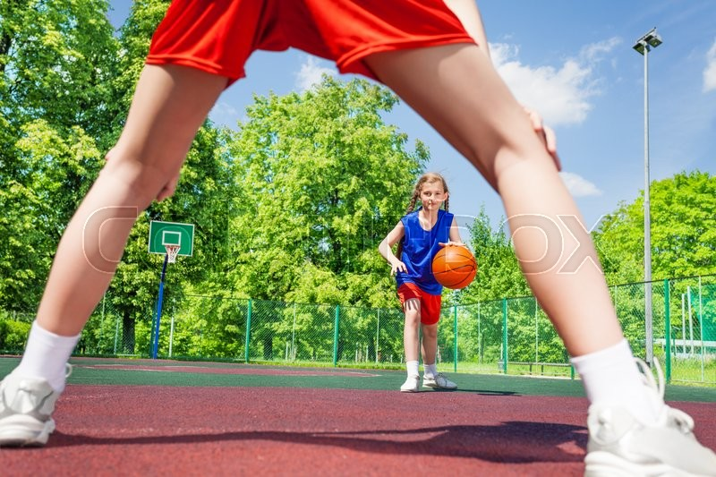 Girl with ball view between two legs of opposite player during basketball game on the playground outside, stock photo