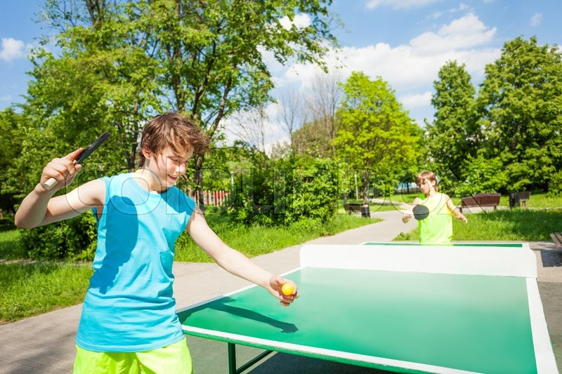 Boy with racket ready to play in table tennis game outside during summer sunny day, stock photo