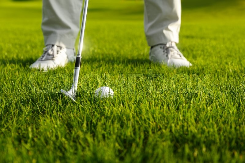 Golf ball and golf club in front of golf player, stock photo