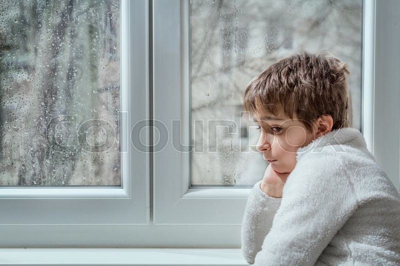 portrait of a pensive young man looking away through a wet window in a rainy day. Toned image, stock photo
