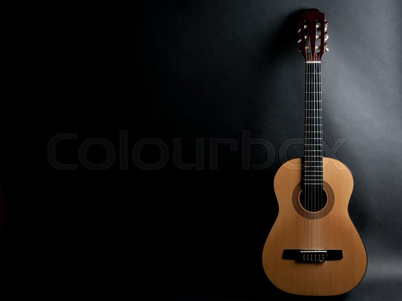 Acoustic guitar on a black background (with copy space), stock photo