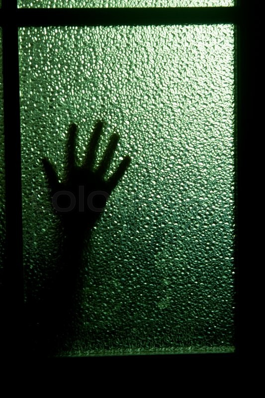 Blurred Silhouette Of A Hand Behind A Window Or Glass Door