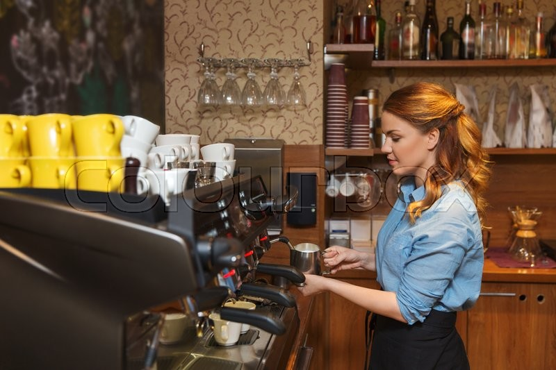 Equipment, coffee shop, people and technology concept - barista woman making coffee by machine at cafe bar or restaurant kitchen, stock photo
