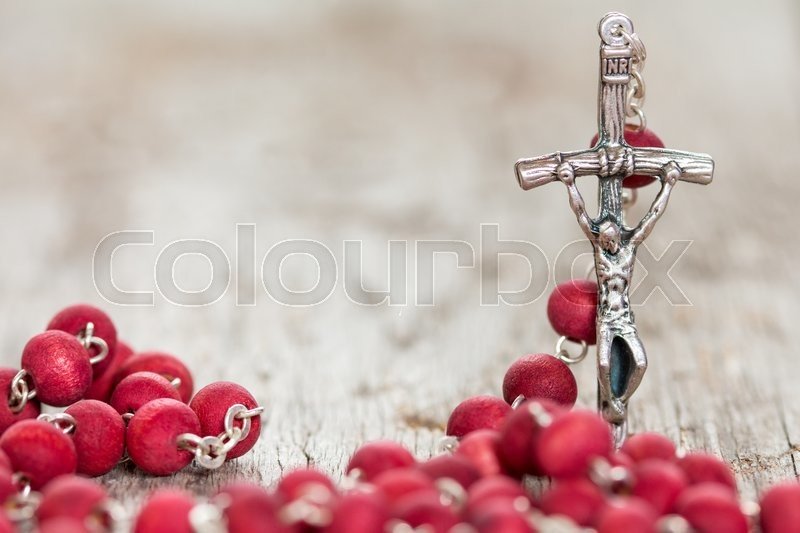 Catholic rosary on old wooden background. Selective focus, stock photo