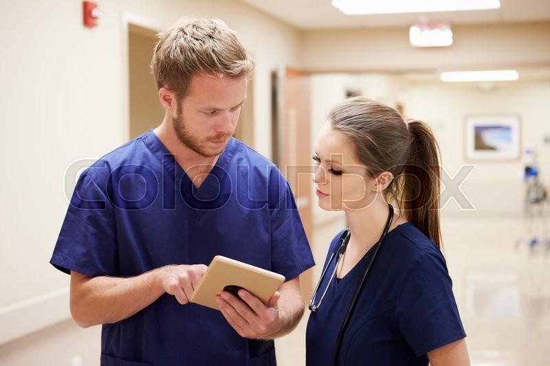 Medical Staff Looking At Digital Tablet In Hospital Corridor, stock photo