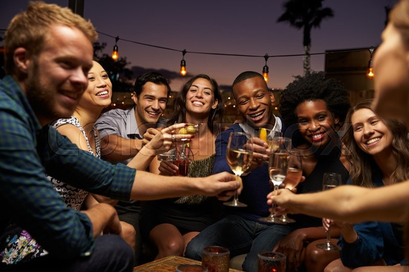 Group Of Friends Enjoying Night Out At Rooftop Bar, stock photo