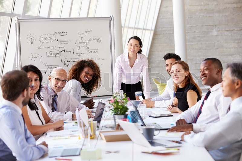 Asian Businesswoman Leading Meeting At Boardroom Table, stock photo