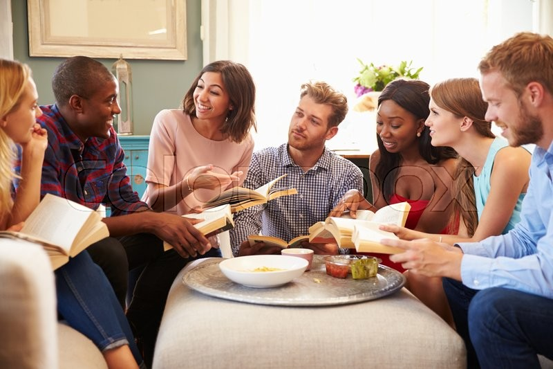 Group Of Friends Taking Part In Book Club At Home, stock photo