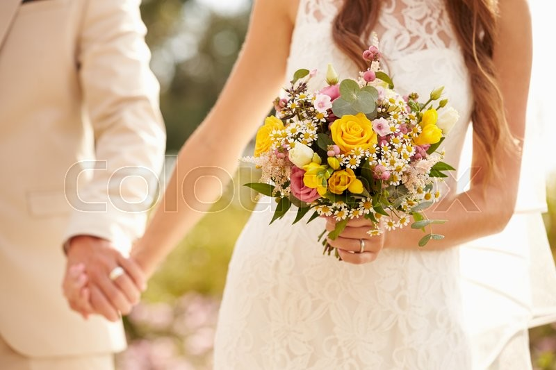 Close Up Of Couple At Wedding Holding Hands, stock photo