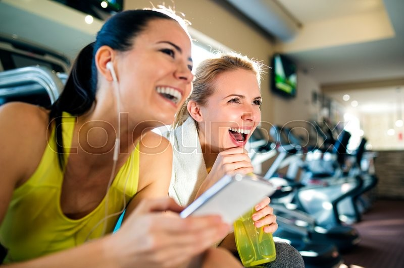 Two attractive fit women in a gym during a break with smart phone laughing, stock photo