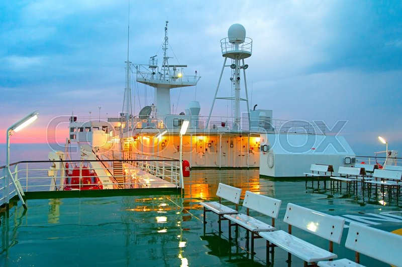 Wet ship deck in the rain at sunset in the sea, stock photo