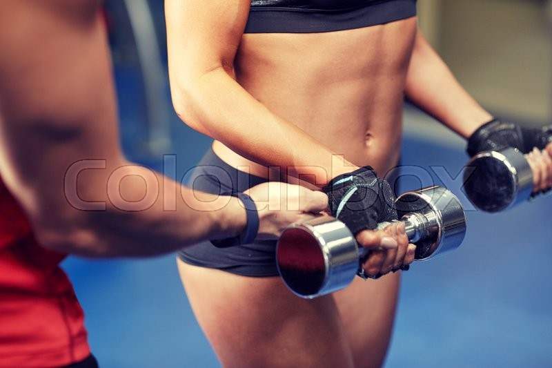Fitness, sport, bodybuilding and weightlifting concept - close up of young woman and personal trainer with dumbbells flexing muscles in gym, stock photo