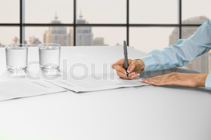 Female office employee signing papers. Female clerk signing office papers. Woman\'s daytime paperwork. Job in big city, stock photo