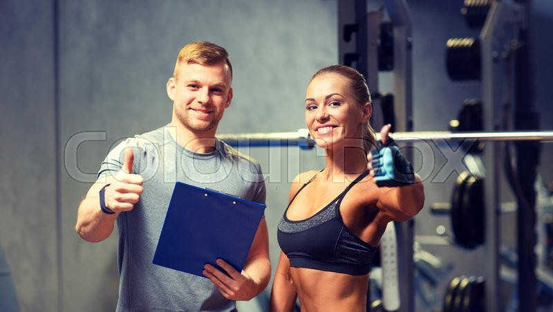 Fitness, sport, exercising and diet concept - smiling young woman and personal trainer with clipboard showing thumbs up in gym, stock photo