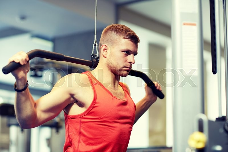 Sport, fitness, bodybuilding, lifestyle and people concept - man exercising and flexing muscles on cable machine in gym, stock photo