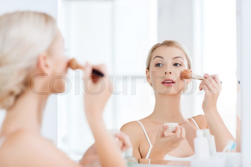 Beauty, make up, cosmetics, morning and people concept - smiling young woman makeup brush and powder foundation looking to mirror at home bathroom, stock photo