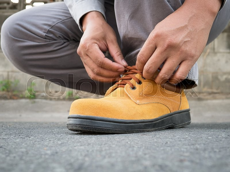 Close up of The man siting to wears safety shoes on street, stock photo