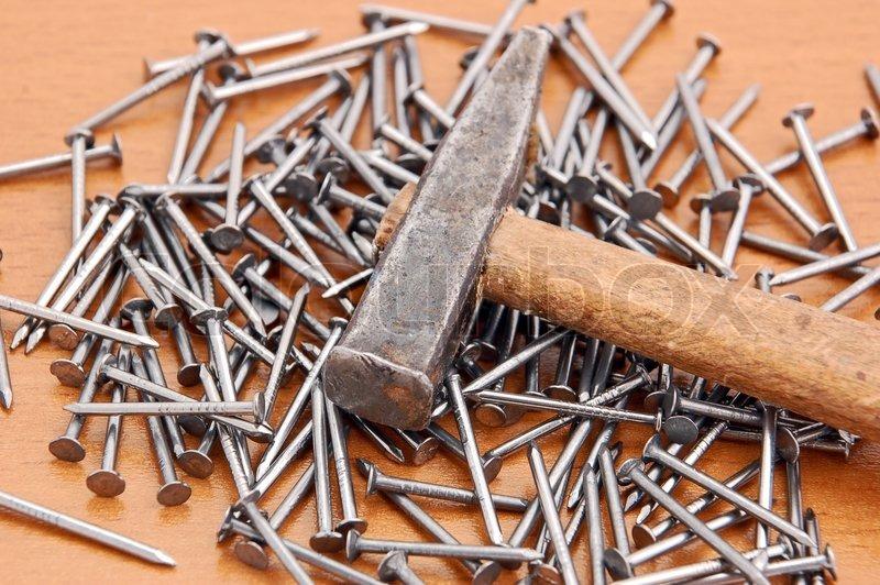 hammer und nagel auf braunen h lzernen hintergrund. Black Bedroom Furniture Sets. Home Design Ideas