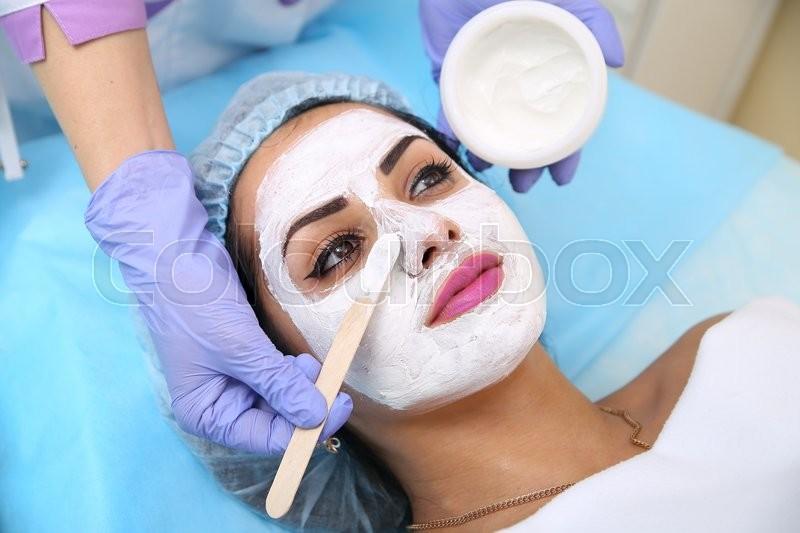 Beautiful woman with facial mask at beauty salon, stock photo