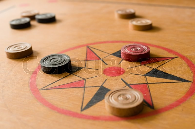 A game of carrom with scattered stones on the board around the center star, stock photo