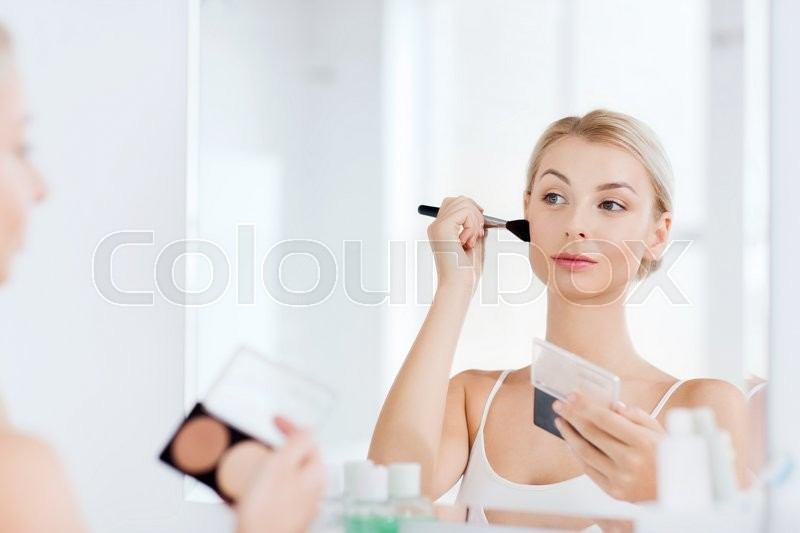 Beauty, make up, cosmetics, morning and people concept - young woman with makeup brush and contouring and highlighting palette looking to mirror at home bathroom, stock photo