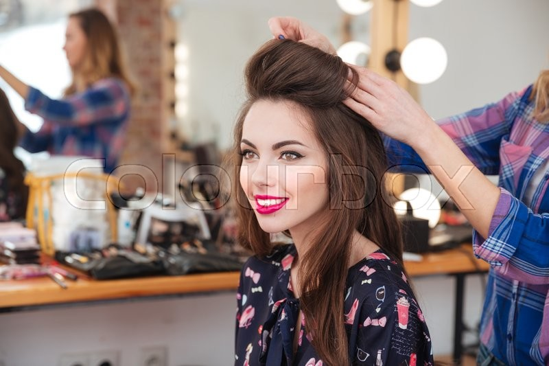 Professional female hairdresser making hairstyle to cheerful young woman with long hair, stock photo