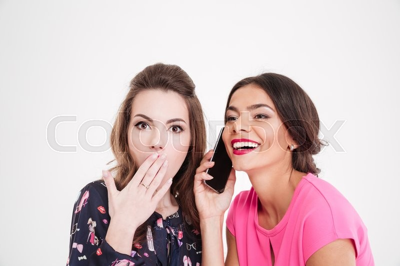 Shocked beautiful young woman overhearing conversation of cheerful female with mobile phone over white background, stock photo
