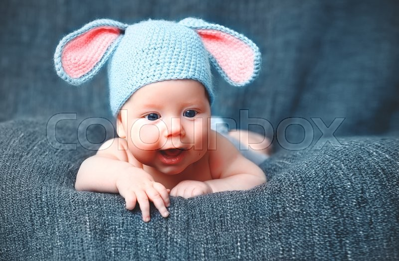 Happy baby child in costume a rabbit bunny on a grey background, stock photo