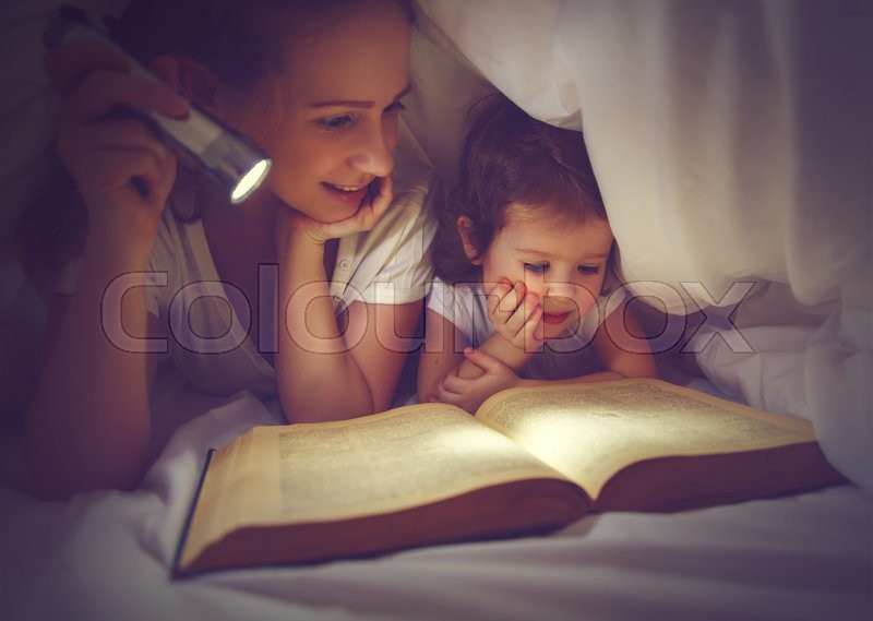 Family reading bedtime. Mom and child daughter reading a book with a flashlight under the blanket in bed, stock photo