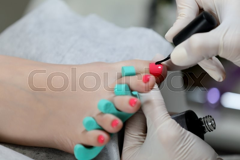 Gel pedicure. Pink color on the nails and white gloves of master ...