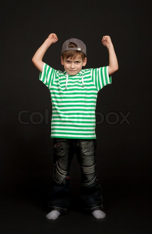 Stock image of 'Boy showing his muscle on black background'