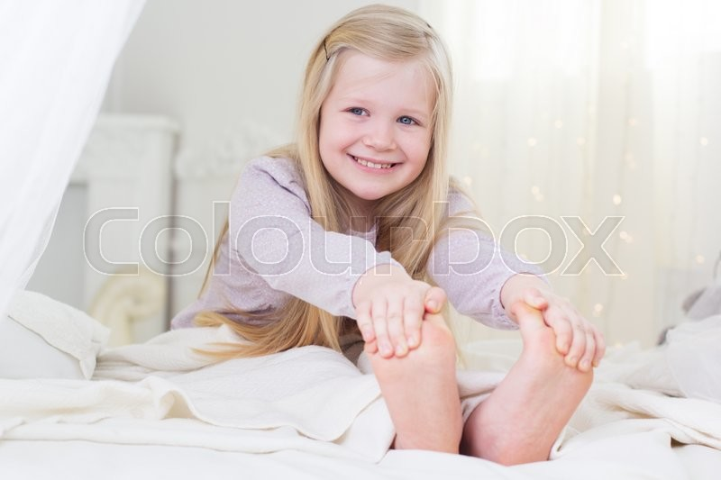 Happy Blonde Child Girl Is Sitting Stock Photo