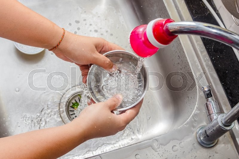 Women washing the pot in sink, stock photo