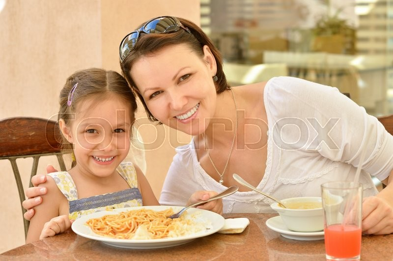 Little girl with mother eating at table, stock photo