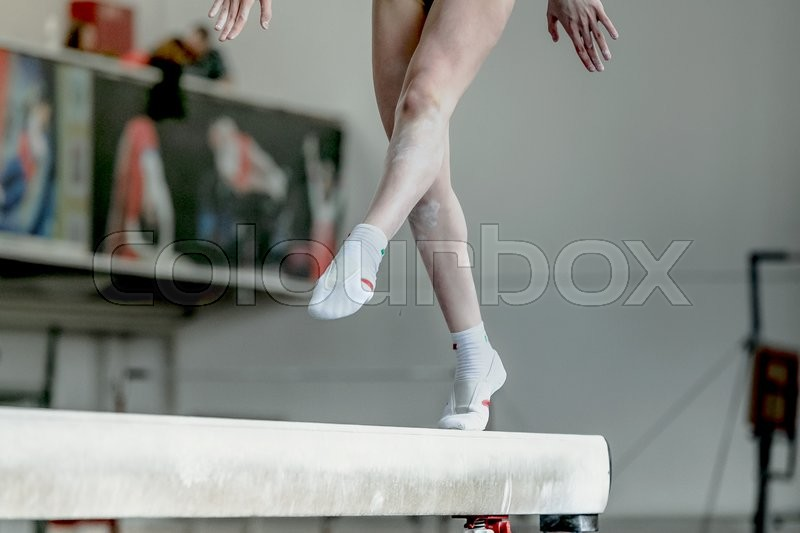 Girl gymnast athlete during exercise on balance beam in gymnastics competitions, stock photo