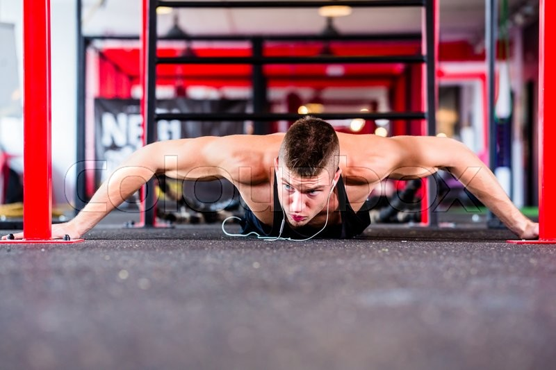 Man exercising doing push-up on floor of sport fitness gym, stock photo