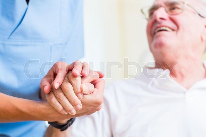 Nurse holding hand of senior man in rest home, stock photo