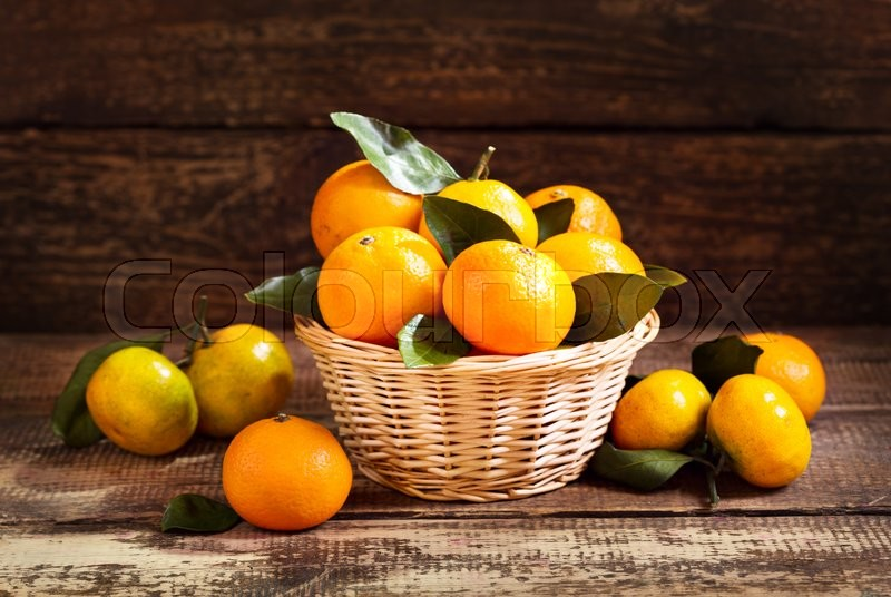 Fresh mandarin oranges fruit with leaves on wooden table, stock photo
