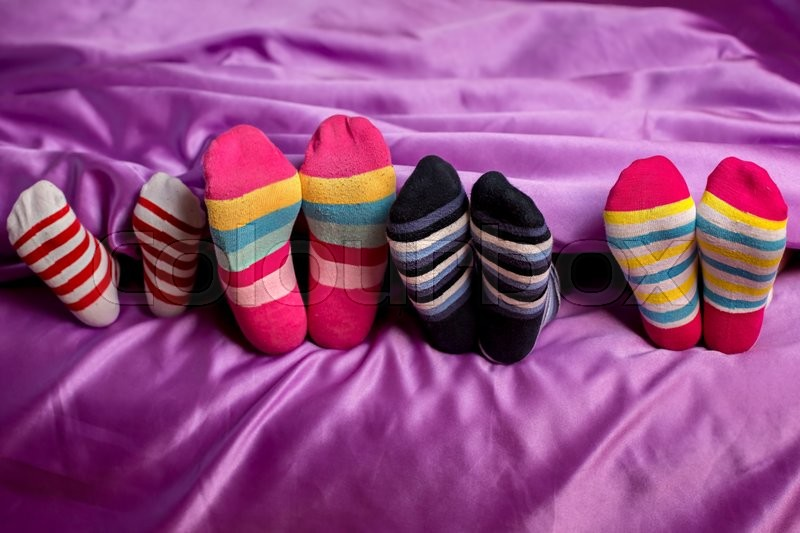 Small feet in colorful socks. Children\'s feet wearing colorful socks. Purple blanket and striped socks. Wear what you want to, stock photo