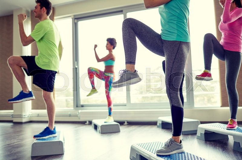 Fitness, sport, aerobics and people concept - group of smiling people working out and raising legs on step platforms in gym, stock photo