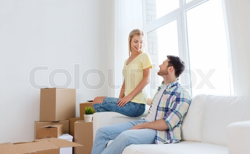 Moving, people, repair and real estate concept - happy couple with big cardboard boxes on sofa at new home, stock photo