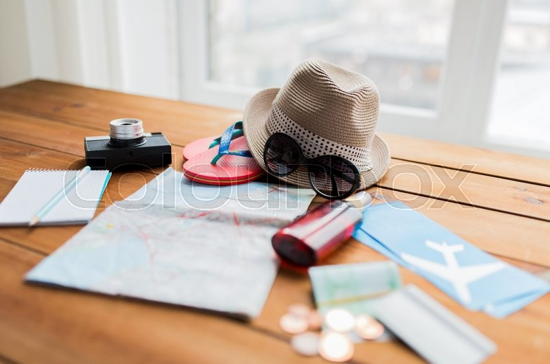 Summer vacation, tourism and objects concept - close up of travel map, airplane tickets, money and personal accessories, stock photo