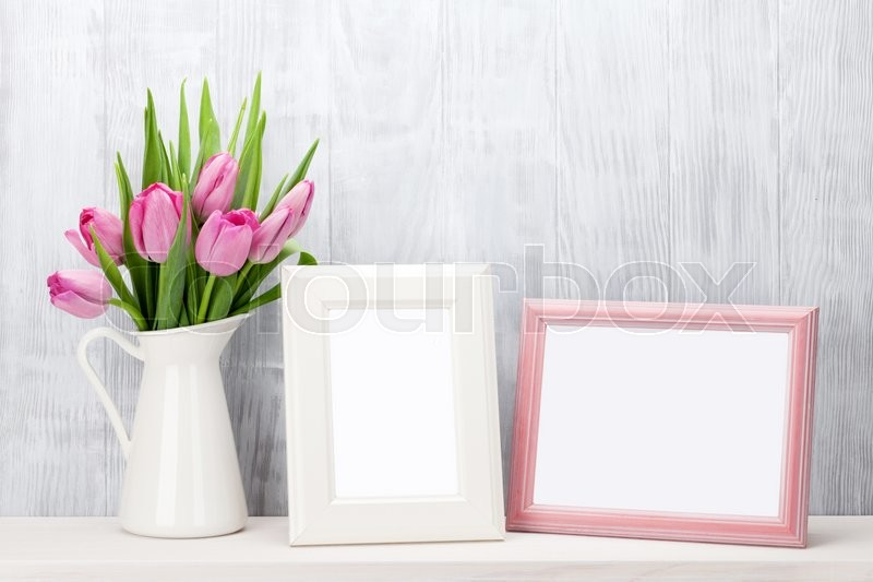 Fresh pink tulip flowers bouquet and blank photo frames with copy space on shelf in front of wooden wall, stock photo